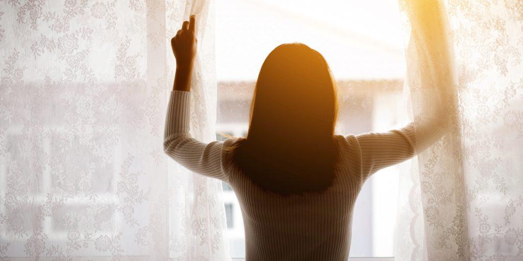 Kvinne står i vinduet med ryggen til, og trekker fra gardinene.