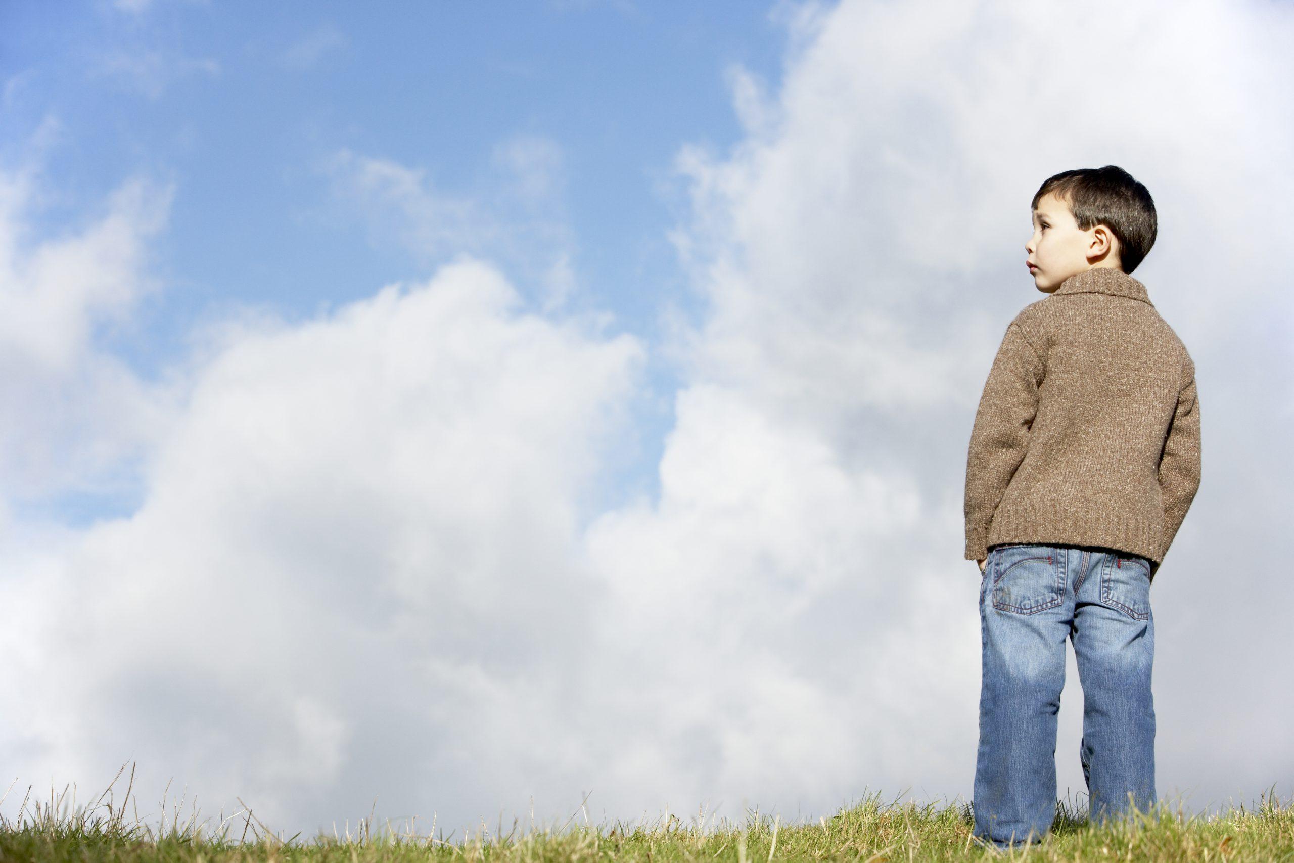 Ung gutt står utendørs med ryggen mot kameraet