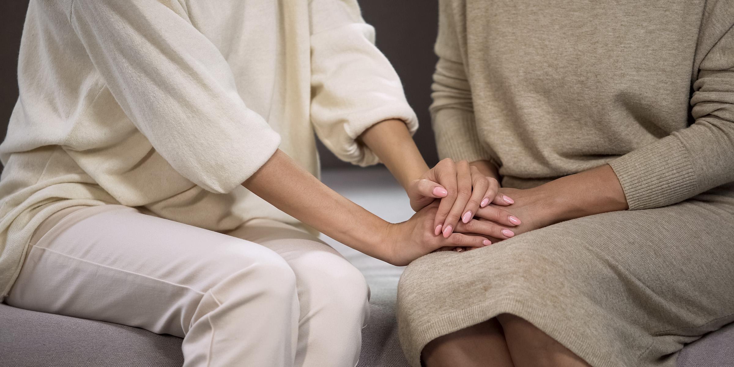 To kvinner holder hverandres hender (illustrasjonsbilde)