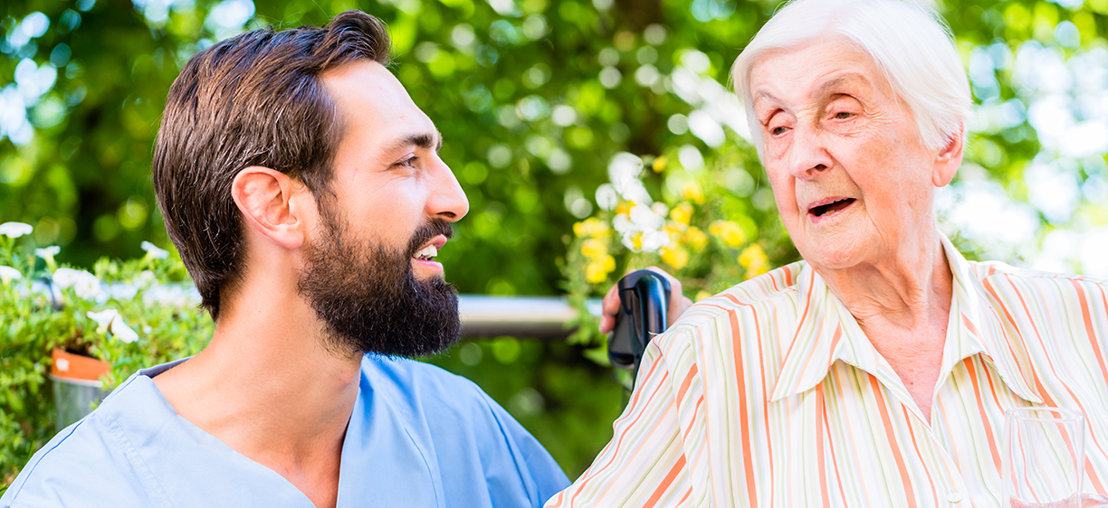 Male nurse listening to older person at nursing home in the garden. Photo: colourbox.com