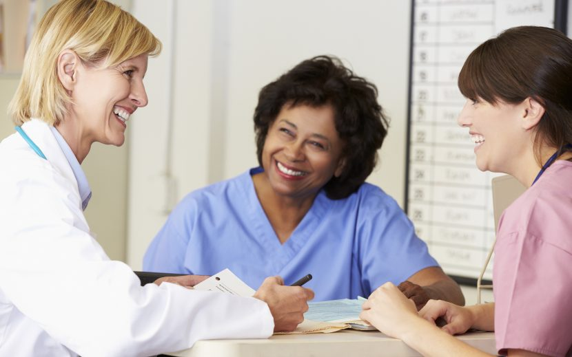 A female doctor talking to two female nurses.