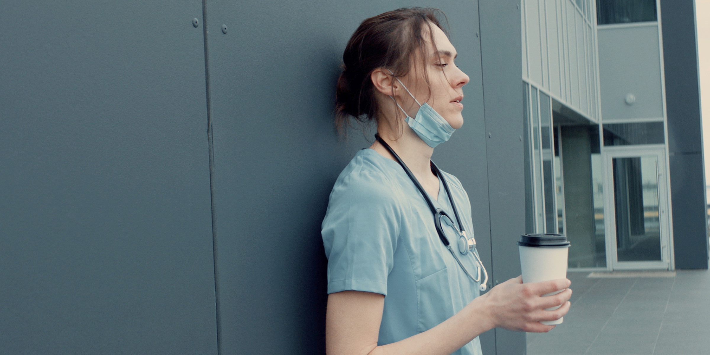 A young nurse looking tired and standing outside sipping coffee