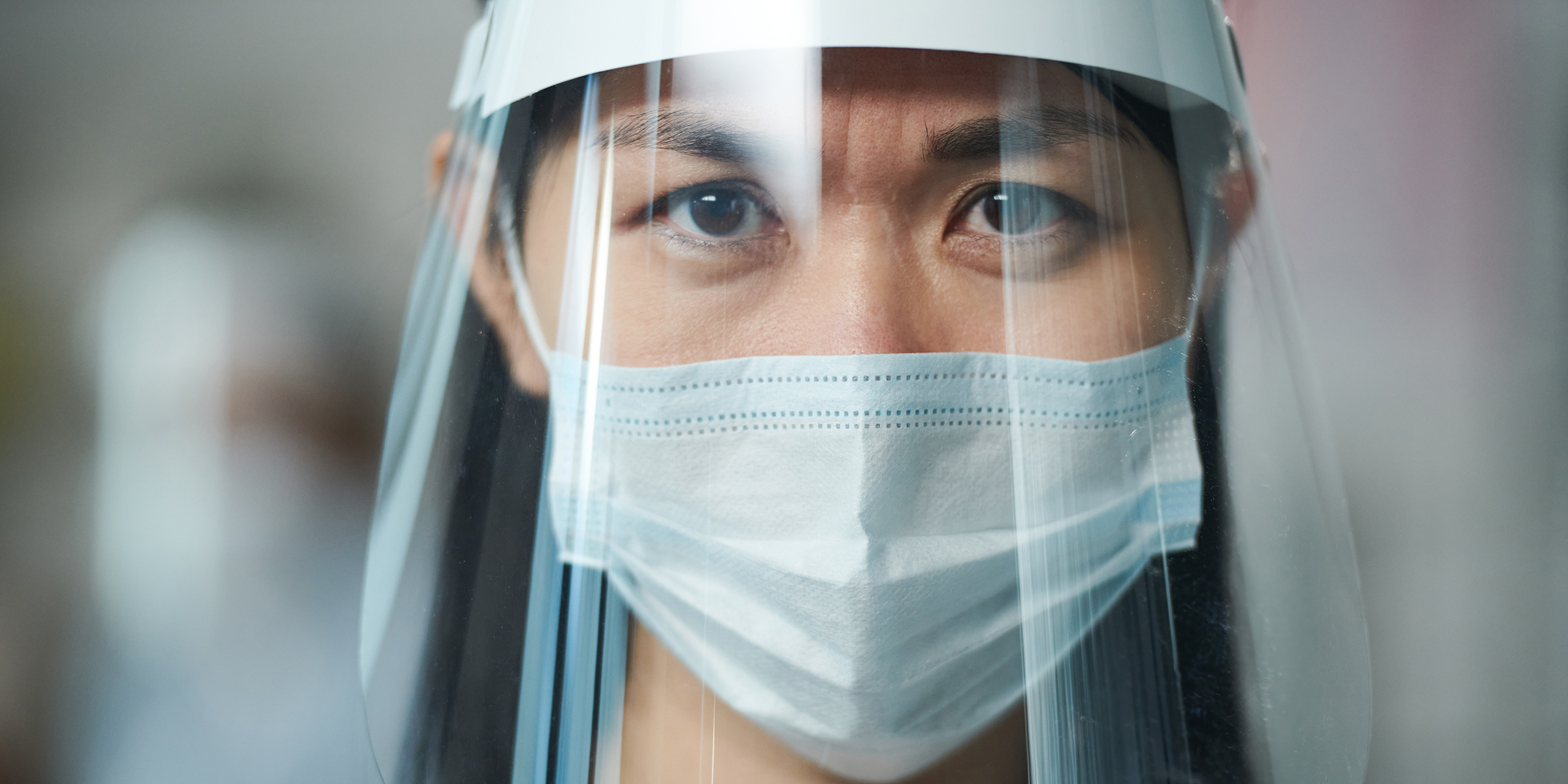 Young serious nurse in uniform and protective workwear looking at you through transparent screen